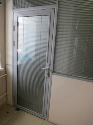 Дверь в алюминиевом окрашенном профиле, цвет RAL 7035, в системе офисных перегородок. Фурнитура: «HOPPE», Германия